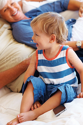 Buy stock photo Little smiling child sitting on sofa with grandparents and looking away