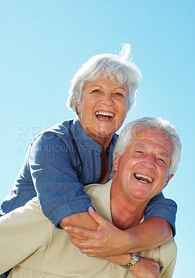 Buy stock photo Portrait of senior couple enjoying a piggyback ride against sky