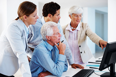 Buy stock photo Senior female executive viewing proposal on computer to her colleagues during a discussion