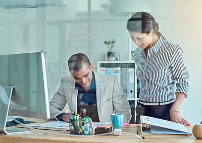 Buy stock photo Cropped shot of two businesspeople looking through some paperwork in an office