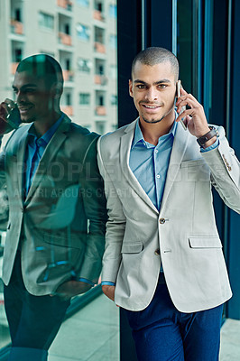 Buy stock photo Portrait of a young businessman using his phone at work