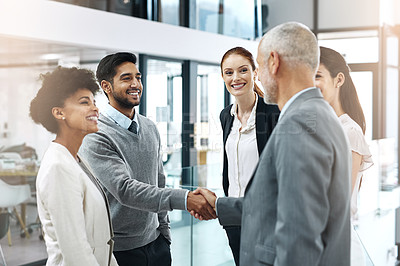 Buy stock photo Shot of two businessmen shaking hands while their colleagues look on
