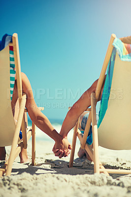 Buy stock photo Rearview shot of a young couple sitting hand in hand on loungers at the beach