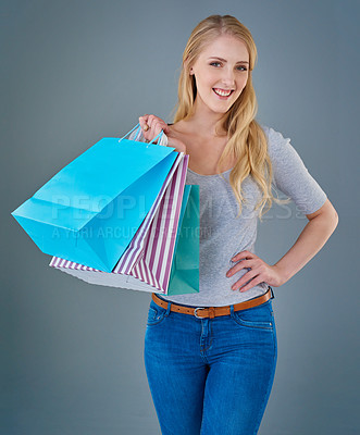 Buy stock photo Cropped studio shot of a young woman holding up a selection of shopping bags