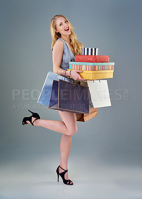 Buy stock photo Full length studio shot of a happy young woman holding a selection of shopping bags and gift boxes