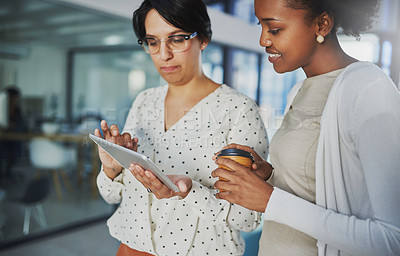 Buy stock photo Cropped shot of two businesswomen looking at a tablet in the office