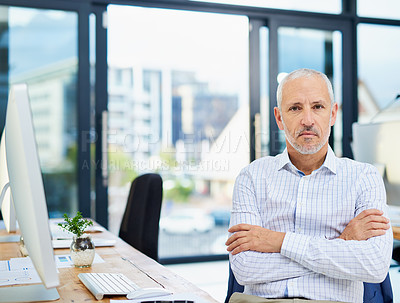 Buy stock photo Cropped portrait of a mature businessman sitting with his arms folded in the office