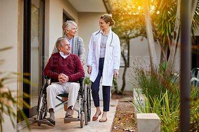 Buy stock photo Shot of a senior couple and a nurse outside a nursing home