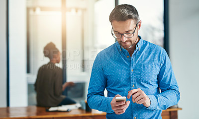 Buy stock photo Cropped shot of a businessman texting on a cellphone in an office