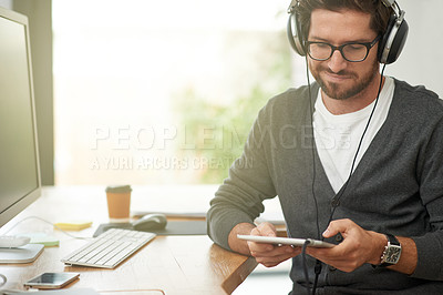Buy stock photo Shot of a young entrepreneur using headphones and a digital tablet at his work desk