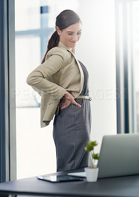 Buy stock photo Shot of a businesswoman suffering from back pain in her office