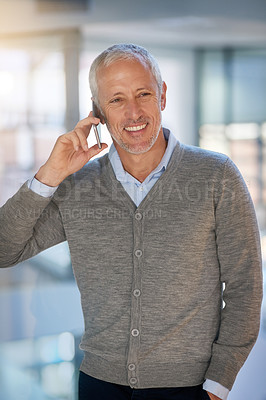 Buy stock photo Shot of a mature businessman making a phonecall while walking in his office