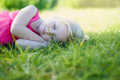 Buy stock photo Cropped shot of a cute little girl sleeping on the grass outside