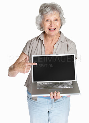 Buy stock photo Portrait of a happy senior woman pointing to a laptop screen isolated against white