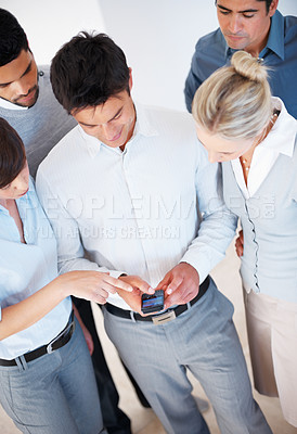 Buy stock photo High angle view of business people sharing information on cell phone
