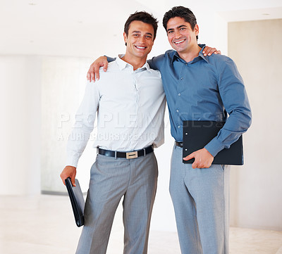 Buy stock photo Portrait of friendly male executives standing with arms around and smiling