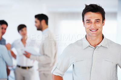 Buy stock photo Portrait of handsome business man with colleagues discussing in background