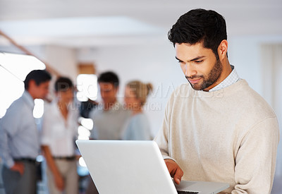 Buy stock photo Business man using laptop with colleagues discussing in background