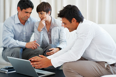 Buy stock photo Consultant explaining investment plans to business couple using laptop