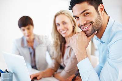 Buy stock photo Portrait of smart male executive sitting at table with hand on chin and colleagues using laptop in background