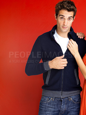 Buy stock photo Portrait of a smart young man with a woman's hands on his shoulder against a red background