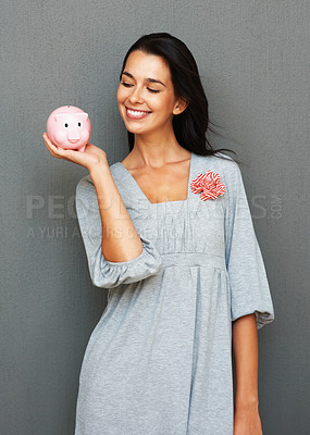 Buy stock photo Happy woman looking at piggy bank she is holding