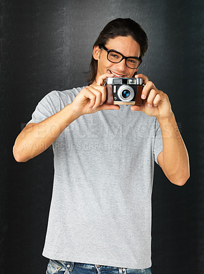 Buy stock photo Man with glasses holding up vintage camera