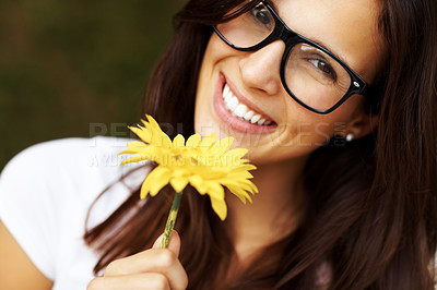 Buy stock photo Portrait of lovely young woman in retro glasses holding a yellow flower and smiling at the camera