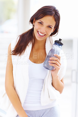 Buy stock photo Portrait of pretty young woman standing in the gym holding a water bottle