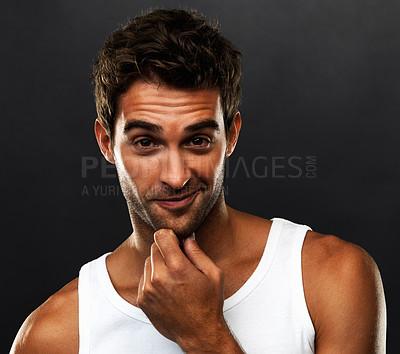 Buy stock photo Closeup portrait of young man smirking on black background