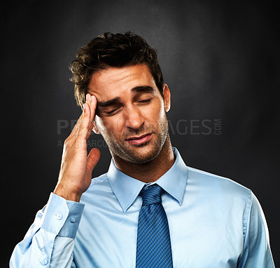 Buy stock photo Closeup of young business man with a migraine massaging his temple on black background