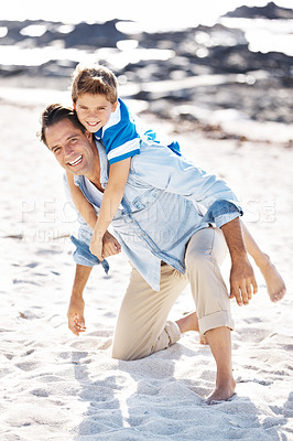 Buy stock photo Happy father carrying his cute little son on his back at the sea shore