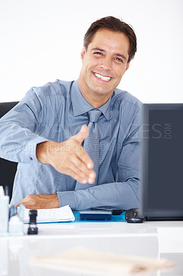 Buy stock photo Portrait of happy male business executive sitting at a desk and offering handshake