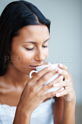 Buy stock photo Relaxed mixed race woman enjoying coffee with eyes closed