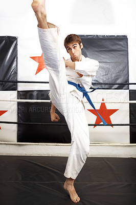 Buy stock photo Full length shot of a young martial artist practicing karate in the ring