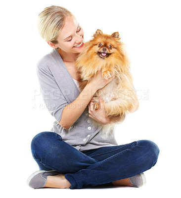 Buy stock photo Lovely blonde sitting with crossed legs holding a cute pomeranian dog
