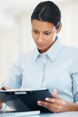 Buy stock photo Modern female professional reviewing documents at workplace