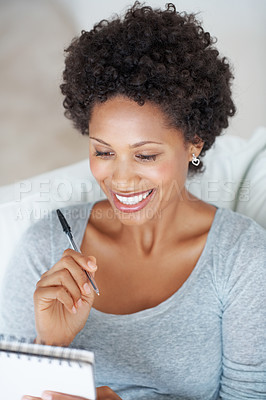 Buy stock photo Smiling African American woman writing on notepad at home