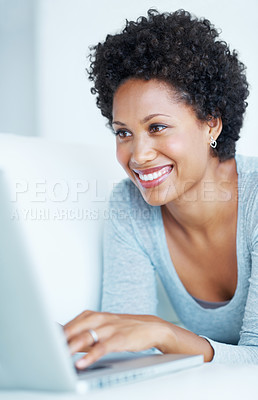 Buy stock photo Attractive young woman using laptop while lying on couch