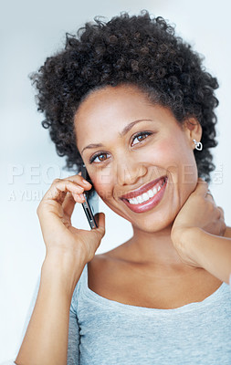 Buy stock photo Closeup of smiling young woman talking on mobile phone over plain background
