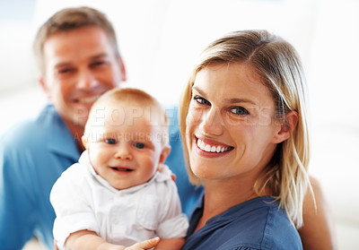 Buy stock photo Portrait of beautiful middle aged woman holding cute baby with smiling man in background