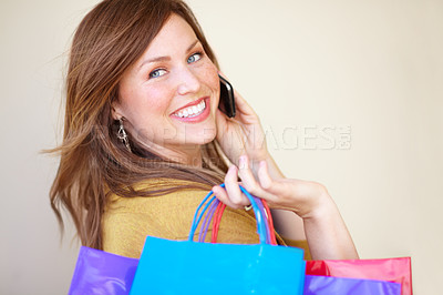 Buy stock photo Cropped shot of a beautiful young woman talking on her cellphone while holding shopping bags