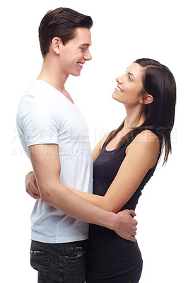Buy stock photo A happy young couple hugging each other while isolated on white