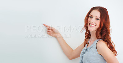 Buy stock photo A beautiful woman pointing at copyspace