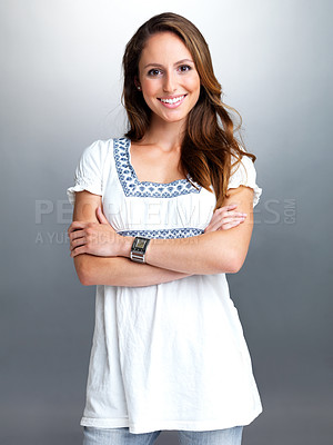 Buy stock photo Portrait of a happy young woman standing with folded hand against grey background