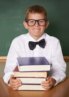 Buy stock photo A happy young schoolboy wearing  glasses and a bow-tie smiling at the camera while sitting with a pile of books