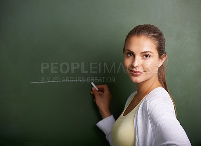 Buy stock photo A beautiful young teacher writing on a blackboard while smiling at the camera - portrait