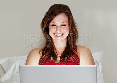 Buy stock photo A beautiful young woman surfing the net while sitting in bed