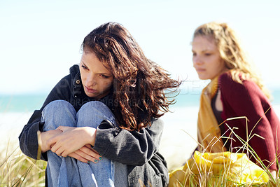 Buy stock photo Shot of two sister's siting apart outside after a disagreement