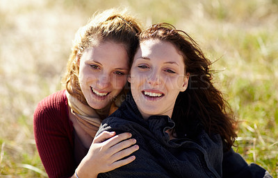 Buy stock photo Portrait of two siblings embracing warmly while sitting outside
